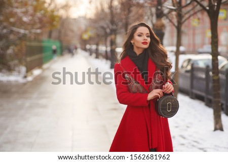 Stunning long-haired brunette woman wearing red maxi coat and holding trendy handbag stands at winter snowy street. Glamorous young female model in luxurious outerwear posing outdoors Royalty-Free Stock Photo #1562681962