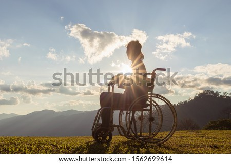 Disabled handicapped woman is sitting on wheelchair at sunset. #1562699614
