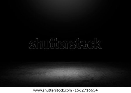 Black background with spotlight to concrete ground in studio. Dark interior background. Room with tile or cement and concrete floor.