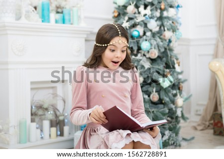 Christmas surprise. Surprised child read surprising story on new year. Small girl keep mouth opened of surprise. Holiday surprise. Find your gift surprise under christmas tree. #1562728891