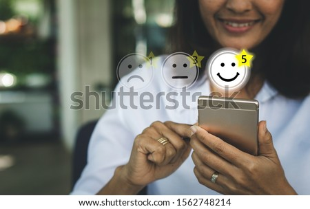 Businesswoman pressing face emoticon on virtual touch screen at smartphone .Customer service evaluation concept. #1562748214