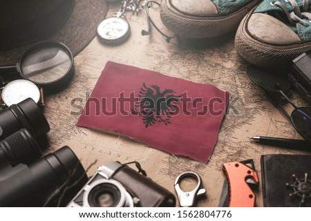 Albania Flag Between Traveler's Accessories on Old Vintage Map. Tourist Destination Concept.  #1562804776