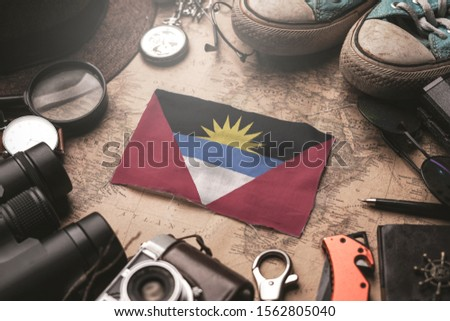 Antigua and Barbuda Flag Between Traveler's Accessories on Old Vintage Map. Tourist Destination Concept.  #1562805040