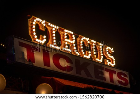 Old dimly lit circus sign with light bulbs in the dark over a ticket stand. Typical view of an entrance to a circus. Concept of fun, family and joy. #1562820700