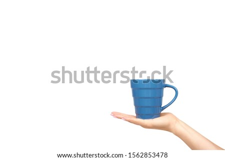Hand with blue ceramic cup, mug for coffee and tea, kitchen pottery. Isolated on white background. Copy space template, mockup. #1562853478