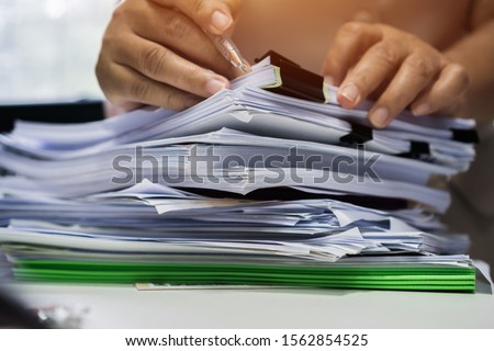 Businessman hands searching unfinished documents stacks of paper files on office desk for report papers, piles of sheet achieves with clips on table, Document is written, drawn,presented. #1562854525