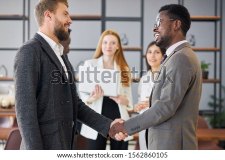 multi-ethnic team after successful meeting shake hands to each other. African and caucasian executives in tuxedo in office #1562860105