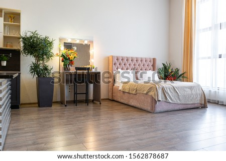 Contemporary ordinary design of spacious studio in soft warm colors. Simple furniture. Light large room with sunlight. Daytime. Tiled brown floor and white walls . #1562878687