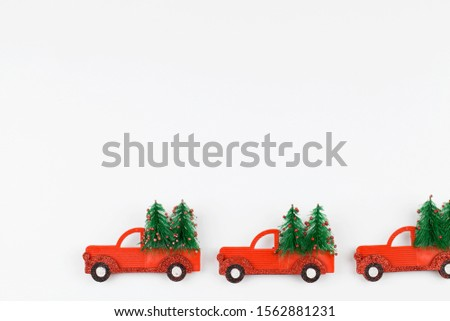 Small toy cars carring christmas tree on white background . Sesonal holidays, greeting card, christmas mood concept. copy space close up