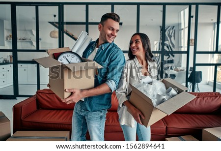 A young married couple in the living room in the house unpack boxes with things. Happy husband and wife are having fun, are looking forward to a new home. Moving, buying a house, apartment concept. #1562894641