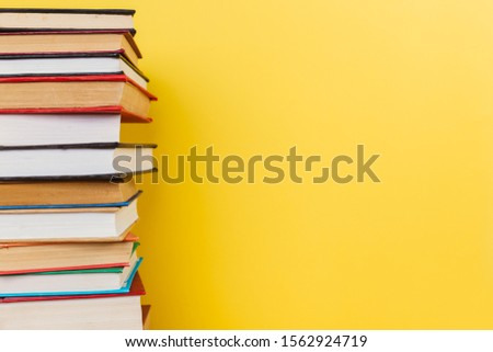 Simple Simple composition of many hardback books, unprocessed books on a wooden table and a yellow background. back to school. Copy space. Education. #1562924719