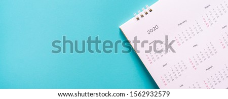 close up top view on white calendar 2020  month schedule to make appointment meeting or manage timetable each day lay on teal background for planning work and life concept #1562932579