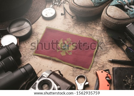 Montenegro Flag Between Traveler's Accessories on Old Vintage Map. Tourist Destination Concept. #1562935759