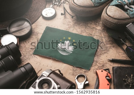 Macau Flag Between Traveler's Accessories on Old Vintage Map. Tourist Destination Concept. #1562935816