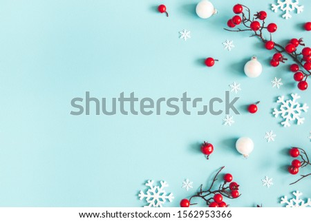 Christmas or winter composition. Snowflakes and red berries on blue background. Christmas, winter, new year concept. Flat lay, top view, copy space #1562953366