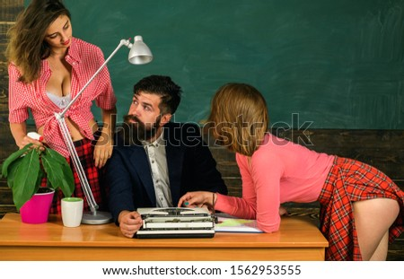 Bearded sexology teacher looks at two sexy female students. Erotic education and sex Symbols on chalkboard. Sex education. Anatomy lesson and sex education in high school. Let's Talk Sex. #1562953555