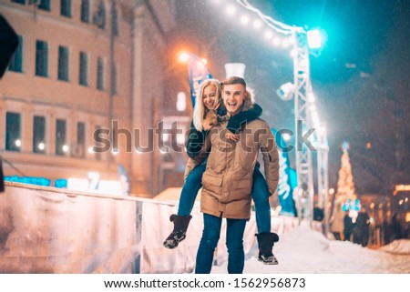 Cheerful and playful couple in warm winter outfits are fooling around #1562956873