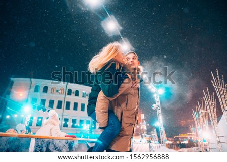 Cheerful and playful couple in warm winter outfits are fooling around #1562956888