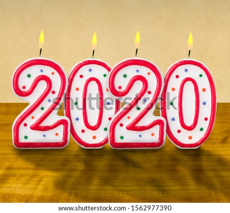 Burning birthday candles on a wooden background - 2020