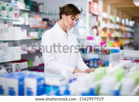 Positive female pharmacist arranging assortment of products in pharmacy #1562997919