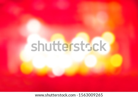 Blurred concert background with vibrant red light on stage.Musical festival wallpaper with bokeh lights.Place text on empty space