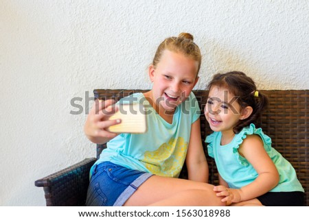 Blue generation. New young celebrity social media star influencer using smartphone, take a picture with her little sister. Happy cute multiracial smiling children taking selfie.