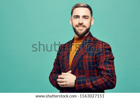 Waist up portrait of successful bearded man smiling at camera while posing against mint green background, copy space