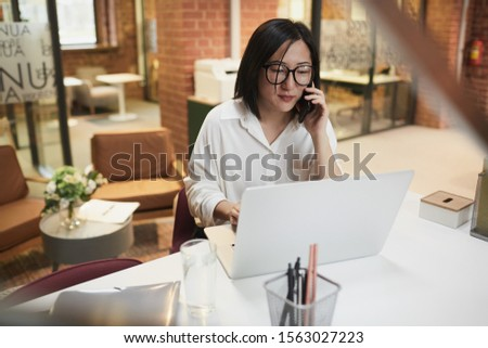 High angle portrait of successful Asian businesswoman sitting at workplace in modern office and speaking by phone while managing deal, copy space #1563027223