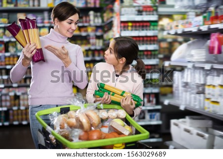 Adult woman with daughter choosing delicious pasta in supermarket #1563029689