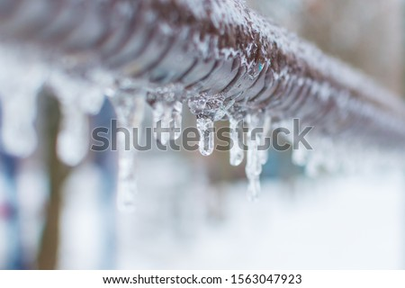 frozen icicles after rain on the pipe Royalty-Free Stock Photo #1563047923