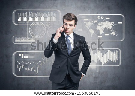 Serious young businessman talking on smartphone near concrete wall with infographics drawn on it. Concept of big data #1563058195