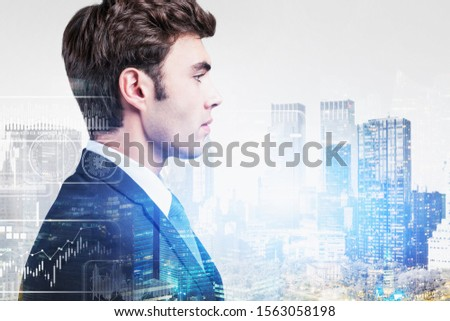Side view of confident young businessman standing in city with double exposure of infographics interface. Toned image #1563058198