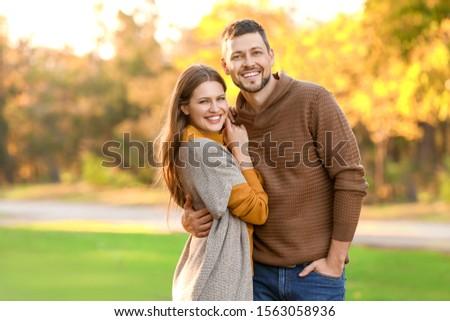 Happy couple walking in autumn park