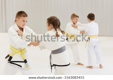 Group of children in white kimono standing and practicing the techniques with each other during training in karate #1563083455