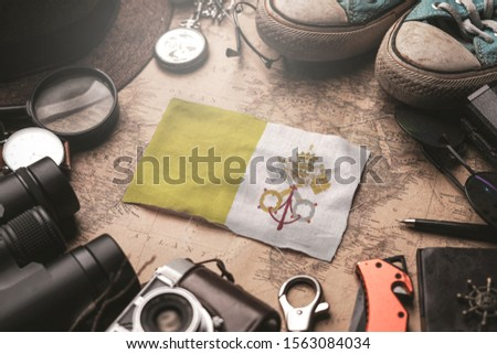 Vatican City Flag Between Traveler's Accessories on Old Vintage Map. Tourist Destination Concept.                    #1563084034