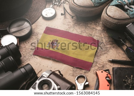 Spain Flag Between Traveler's Accessories on Old Vintage Map. Tourist Destination Concept.                    #1563084145