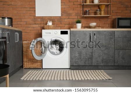 Interior of kitchen with modern washing machine #1563095755