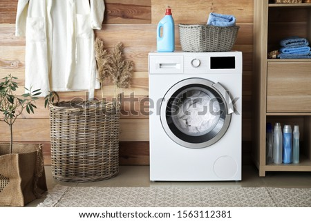 Interior of home laundry room with modern washing machine #1563112381