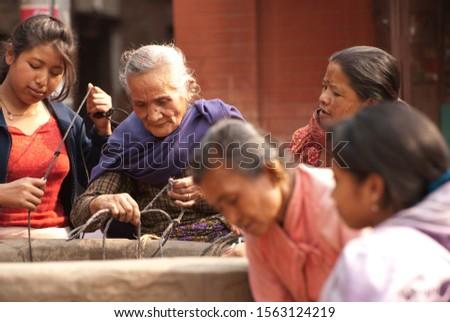 Bhaktapur, Nepal, April 2009. Women get drinking water from a street well. #1563124219