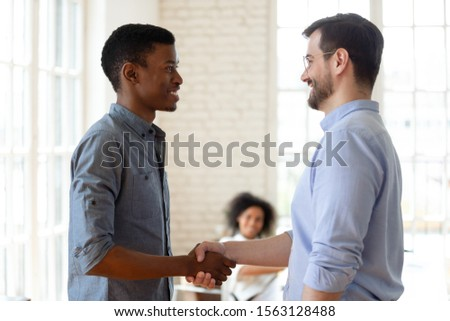 Head shot side view confident company leader in eyeglasses shaking hands with happy african american young employee, thanking for good job. Pleasant boss praising promoting biracial worker at office. #1563128488