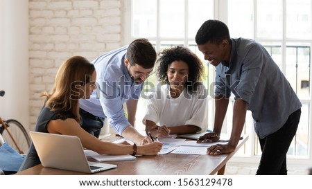 Smiling mixed race colleagues leaning over table, explaining project ideas to female teammates. Happy managers working with project statistics or marketing strategy at brainstorming meeting at office. Royalty-Free Stock Photo #1563129478