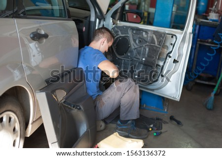 Car master mechanic works on the interior of a car door at vehicle service workshop #1563136372
