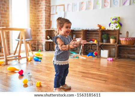 Beautiful toddler standing on the floor applauding and smiling at kindergarten #1563185611