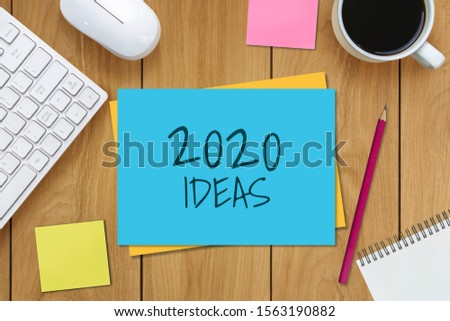 New Year Resolution Goal List 2020 - Business office desk with notebook written in handwriting about plan listing of new year goals and resolutions setting. Change and determination concept. #1563190882