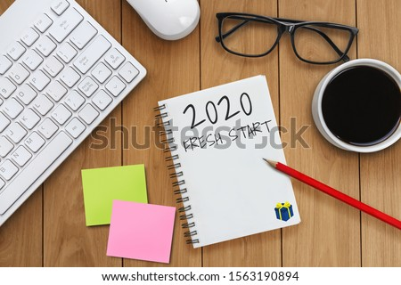 New Year Resolution Goal List 2020 - Business office desk with notebook written in handwriting about plan listing of new year goals and resolutions setting. Change and determination concept. #1563190894