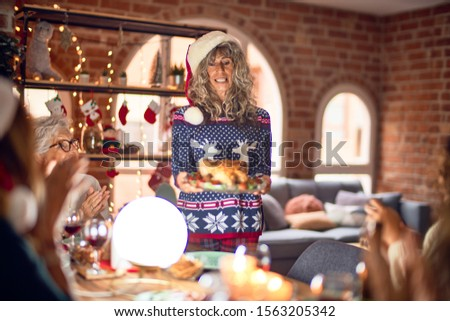 Beautiful group of women smiling happy and confident. Showing roasted turkey celebrating christmas at home #1563205342
