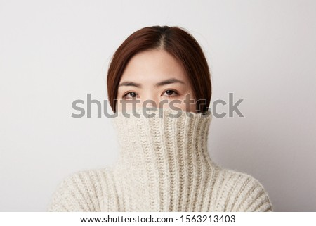 Close-up portrait of Chinese young woman posing on the white background. Isolated. #1563213403