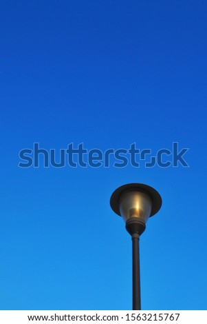 Illumination in outdoor parks with blue background.Modern street lamp against the blue sky without clouds #1563215767