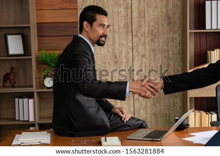 Smart Asian business man in formal suit with beard shaking hands finishing sign contract business deal with partner at workplace office, mature business executive shake hands for agreement discussion #1563281884