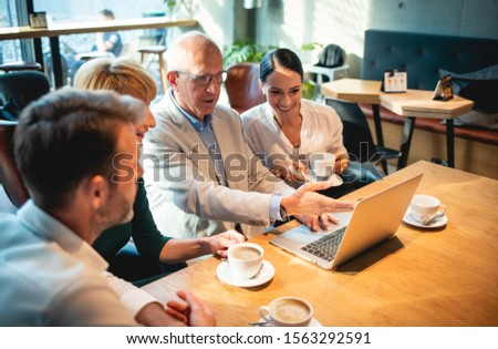 Business people looking at laptop at cafe and discussing #1563292591